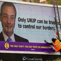 Black man pasting a UKIP election immigration poster advert for Nigel Farage in Thanet. © Jess Hurd/reportdigital.co.uk