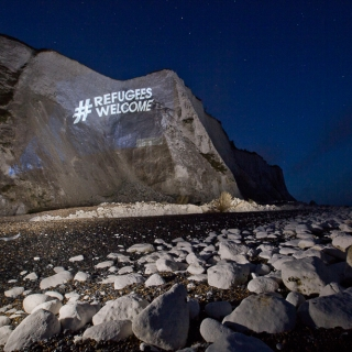 """Refugees welcome"" projected in giant letters across the white cliffs of Dover, ahead of anti immigration protests in Dover. © Jess Hurd/Global Justice Now"